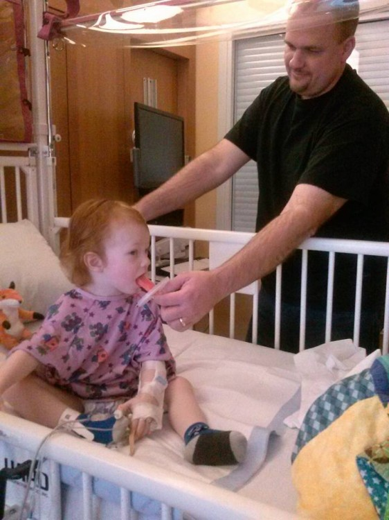 Dad standing next to child's hospital bed