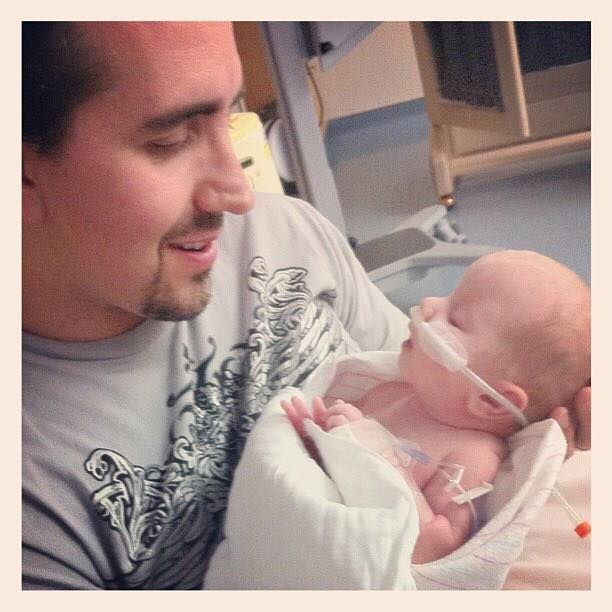Dad holding and looking down at baby in hospital