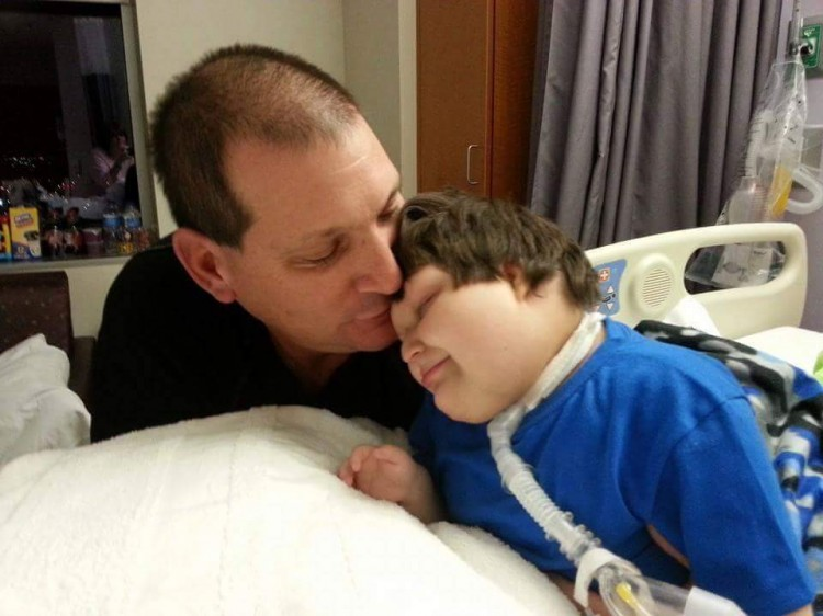 Dad giving child on hospital bed a kiss on the forehead