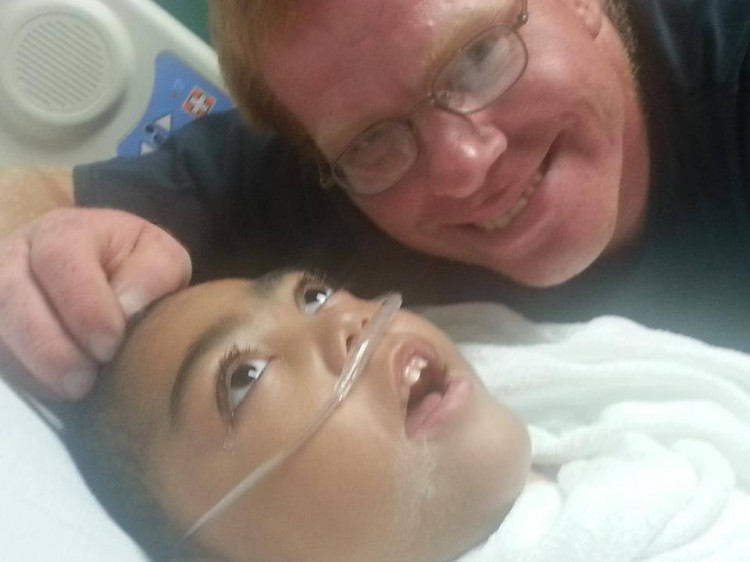 Dad smiling next to child in the hospital