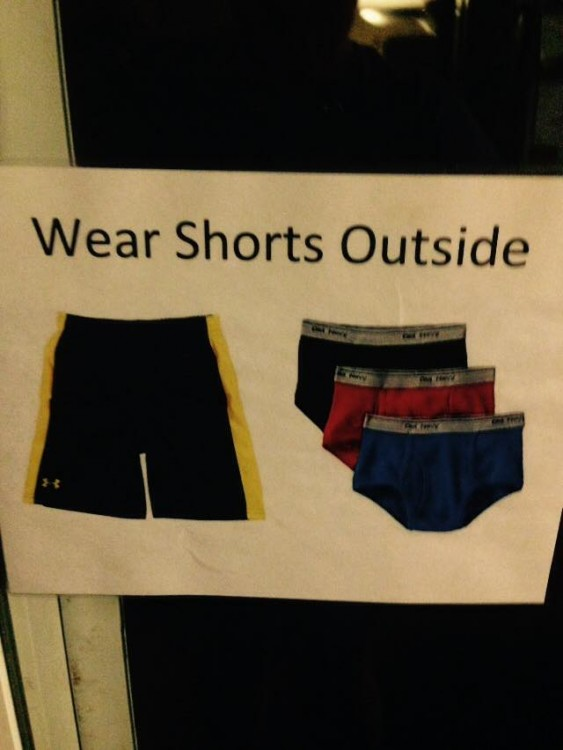 "A sign that says ""Wear Shorts Outside"" and as a picture of a pair of black shorts with a yellow stripe and pairs of black, red and blue underwear"