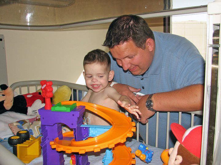 Dad standing next to hospital bed with baby and toys