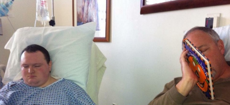 Dad next to son in hospital bed, dad holding a book next to his face