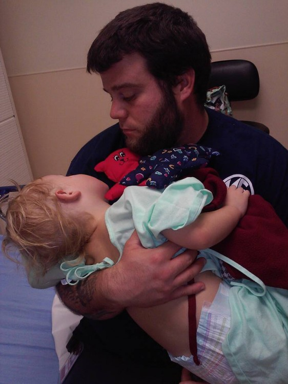 Dad holding child and stuffed animals in hospital