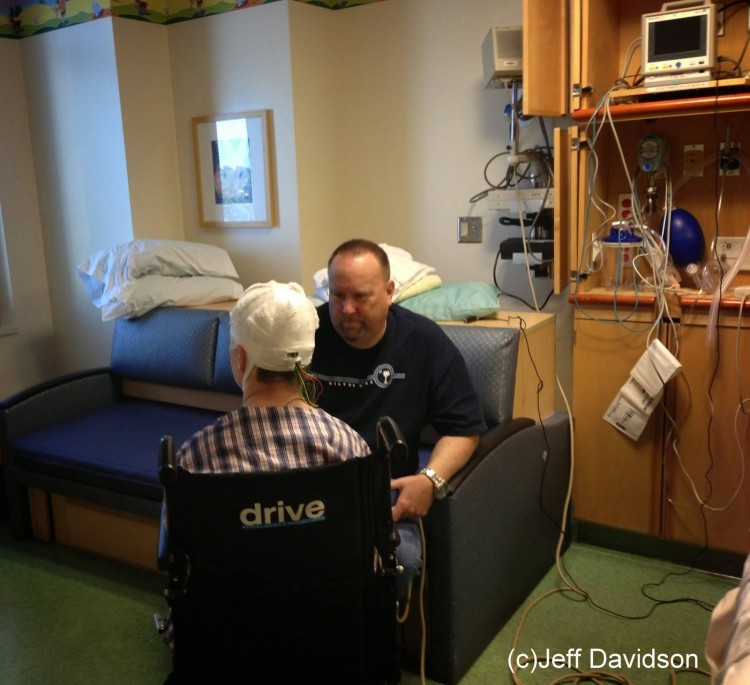Dad sitting in front of son in a wheelchair in the hospital