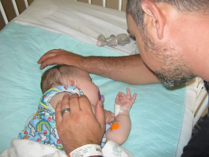 Dad touching arm of baby in hospital crib