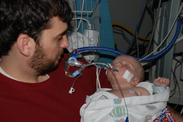 Dad in red shirt holding baby in hospital
