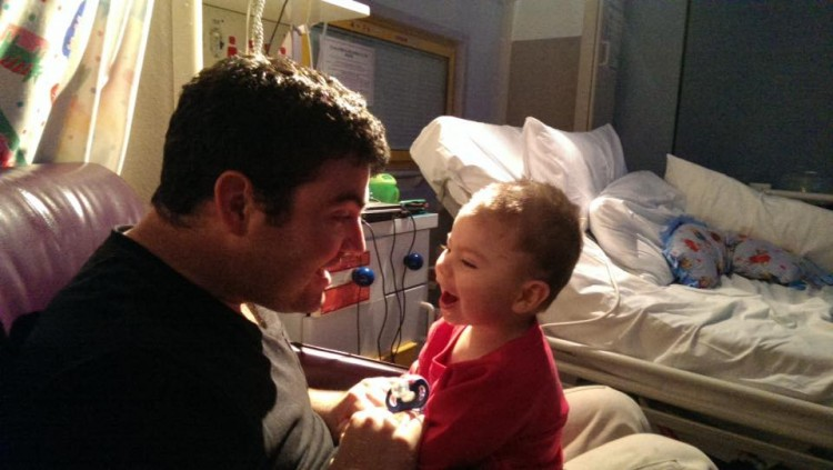 Dad and child laughing together next to hospital bed