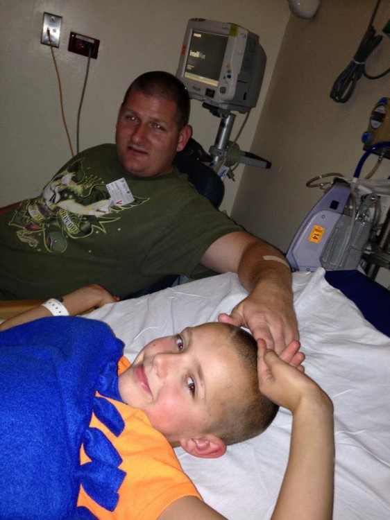 Dad touching head of son in hospital bed