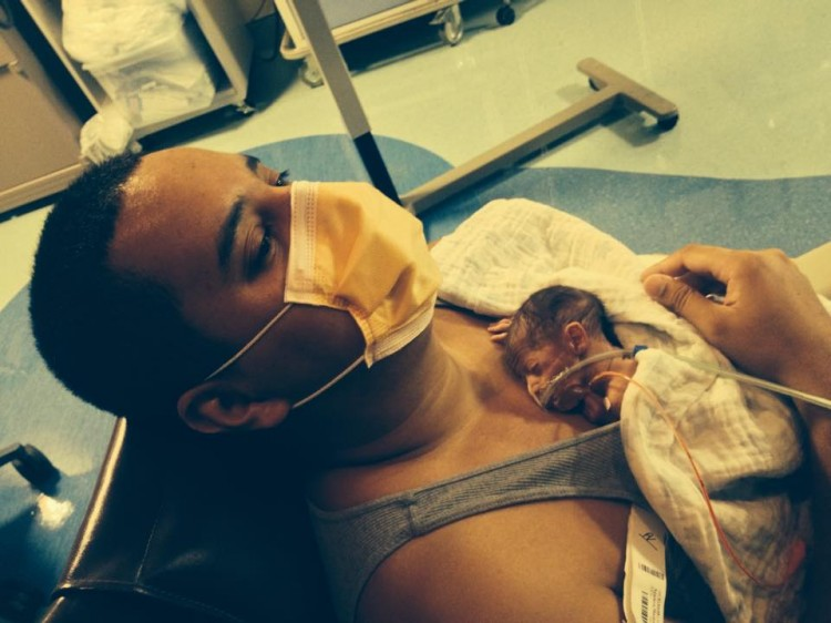 Dad wearing face mask and holding baby in NICU