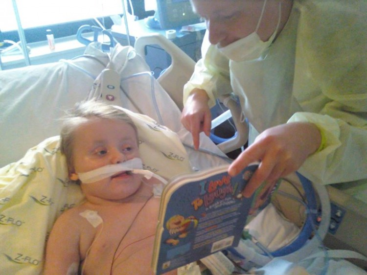Dad reading to child in hospital bed