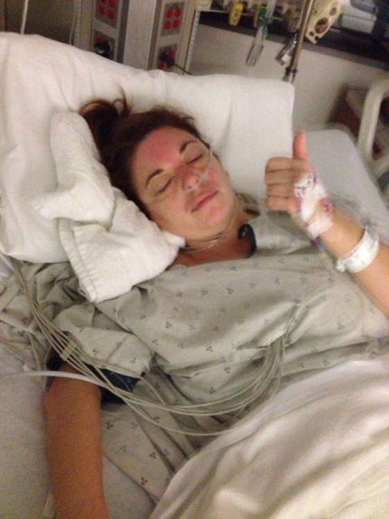 Kerri lying in a hospital bed with her eyes closed, giving the thumbs up