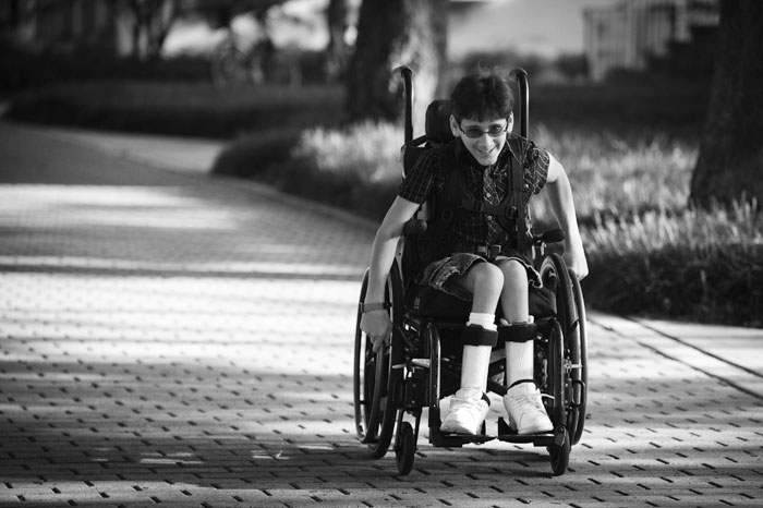 Black and white photo of young adult in a wheelchair on a sidewalk