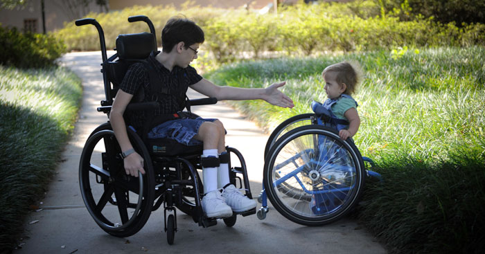 Two people on a sidewalk, one a young adult in a wheelchair holding his hand out to a young boy using assistive walking equipment