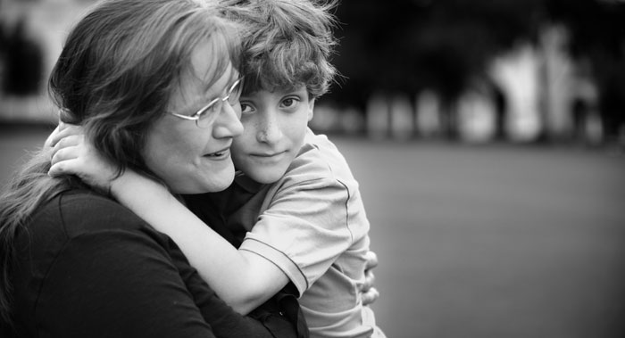 Black and white photo of woman with glasses hugging child