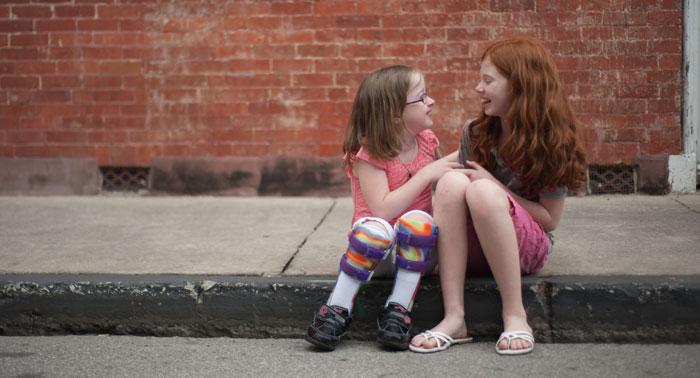 Two girls sitting on the sidewalk
