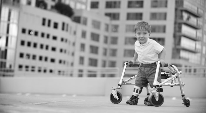 Black and white photo of little boy using a walker