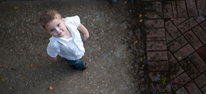 Little boy in white shirt looking up at the camera