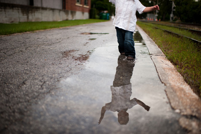 Boy in white shirt standing in puddle on a street