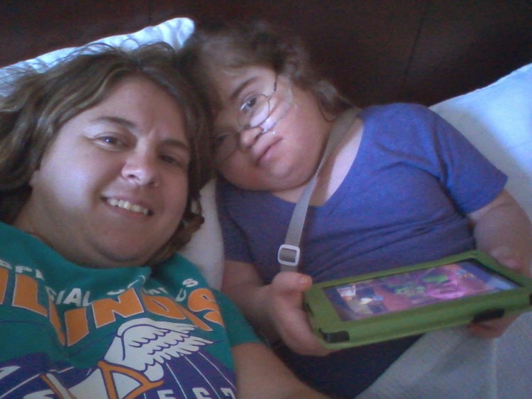woman laying down next to her daughter playing on an ipad