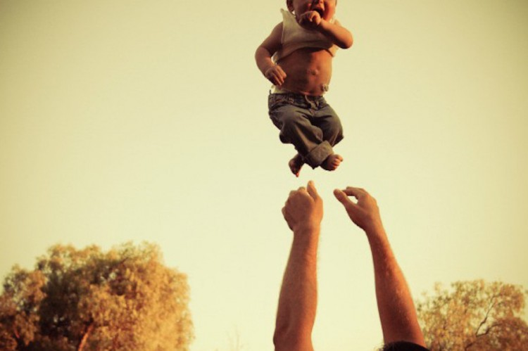 arms throw a baby boy into the air