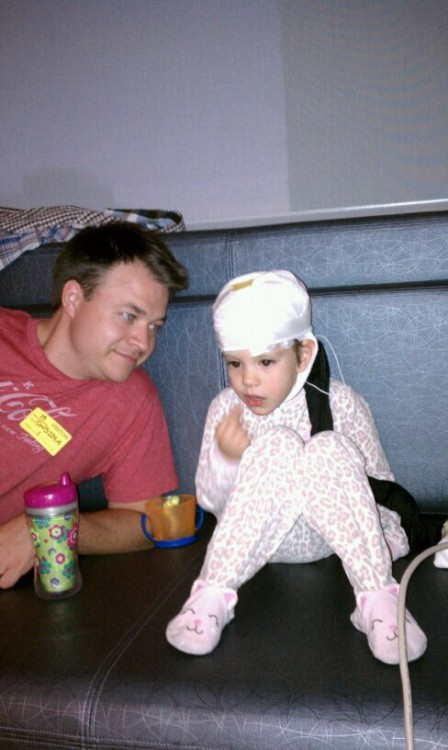 Dad next to daughter on hospital couch