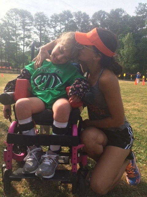 mother kissing daughter in wheelchair