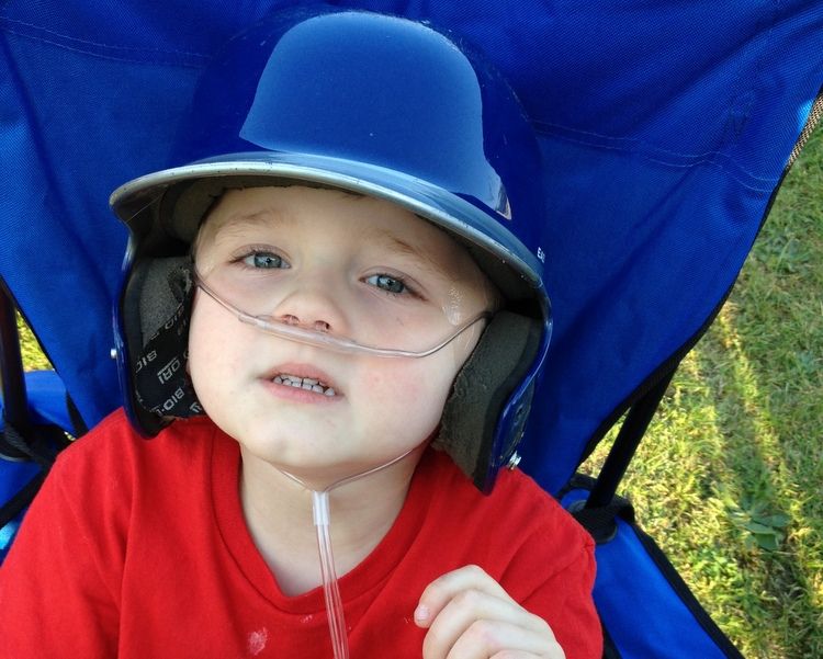 boy with mitochrondrial disease wearing a t-ball helmet
