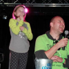 A man singing into a microphone next to two small boys, who are also singing in a microphone
