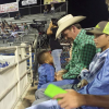 The author's son standing in front of man at rodeo