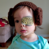 Small female toddler with a 'Star Wars' eye patch and ear muffs on