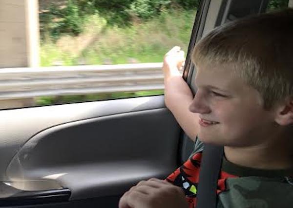 Author's son riding in the passenger seat of a car with window down.
