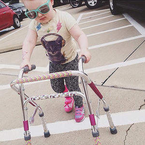 A small girl wearing sunglasses uses a walker to cross a parking lot