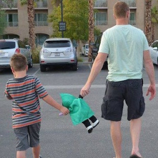 Father and son in a parking lot. Both are holding a toy.