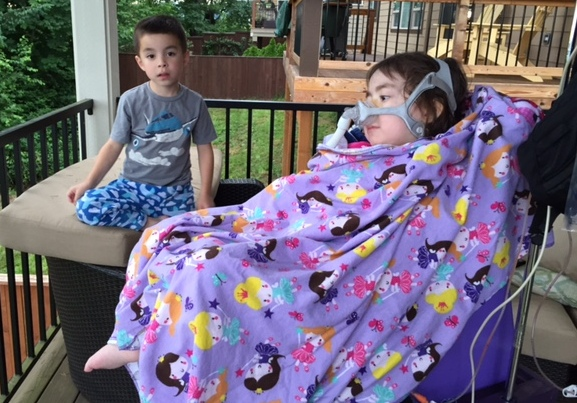 MIchelle's daughter outside in wheelchair with brother