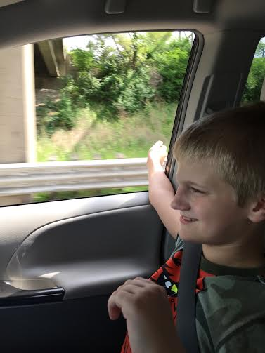 son sitting in car with hand out the window