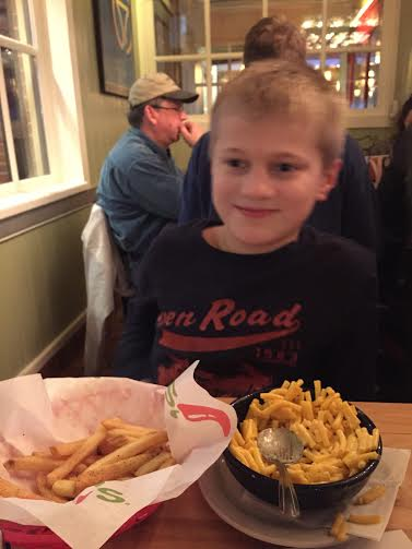 author's son at a restaurant eating fries and macaroni