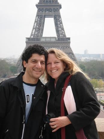 husband and wife standing in front of the eiffel tower