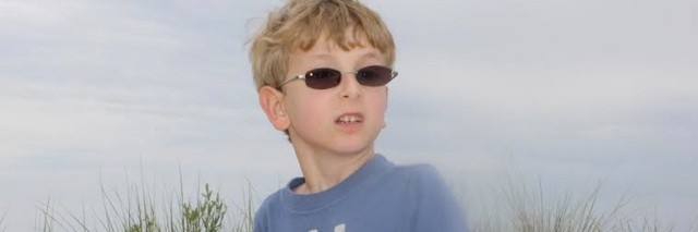 young boy with glasses on the beach