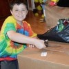 boy in tye dye tshirt smiling and opening a package