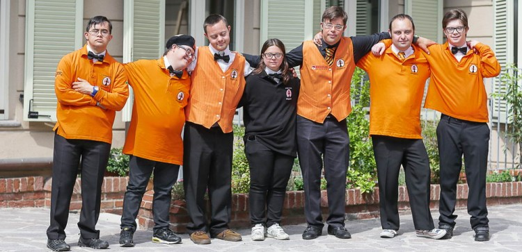Group photo of the employees outside the hotel wearing orange uniforms.