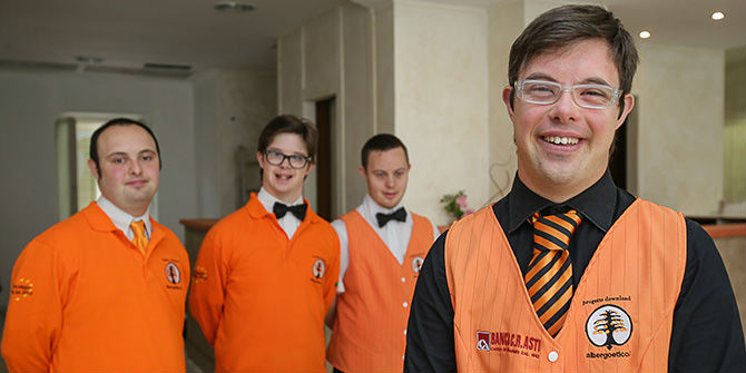 The employees stand in the hotel, smiling with orange uniforms.
