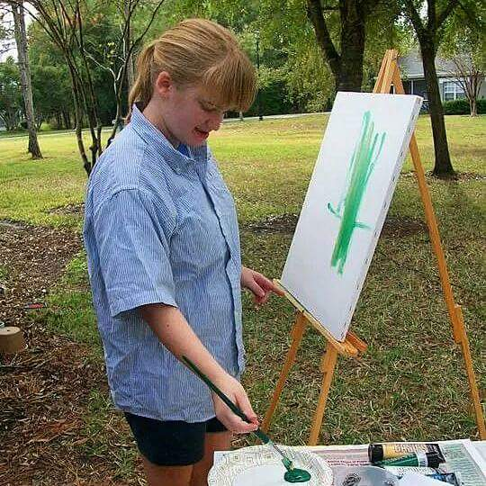 girl painting on an easel at a group home