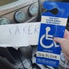 faker sign next to disabled placard for car