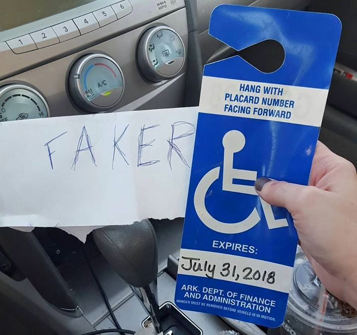 woman holds up faker sign left on her car
