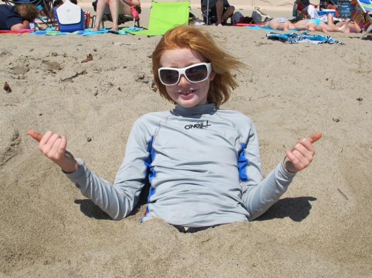 young girl at the beach partly buried in the sand