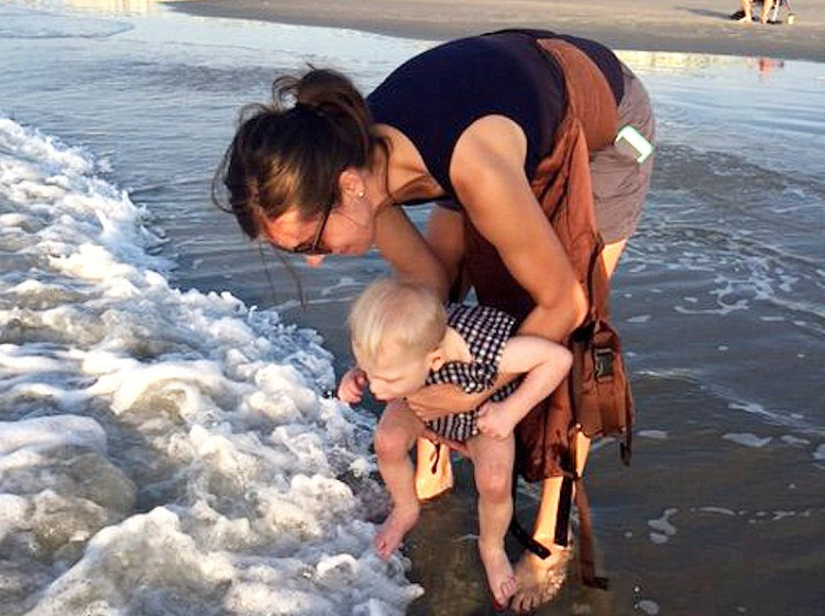 The author with her son at the beach. He's dipping his toes in water while she holds him.
