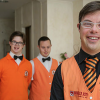 Three men who are hotel staff smile for camera inside hotel