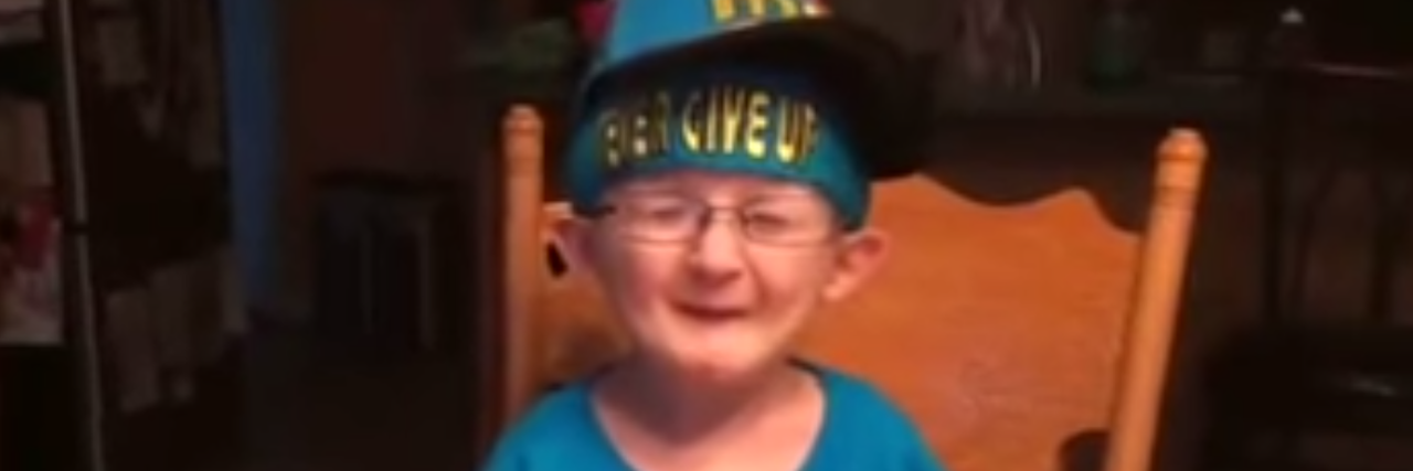 A boy with glasses and wearing a hat sitts at a table as he talks into the camera