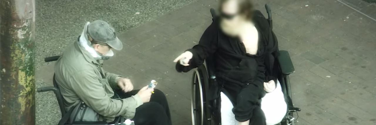two men in wheelchairs talking